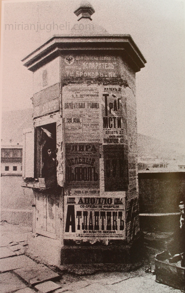 Newspaper booth with posters and ads.